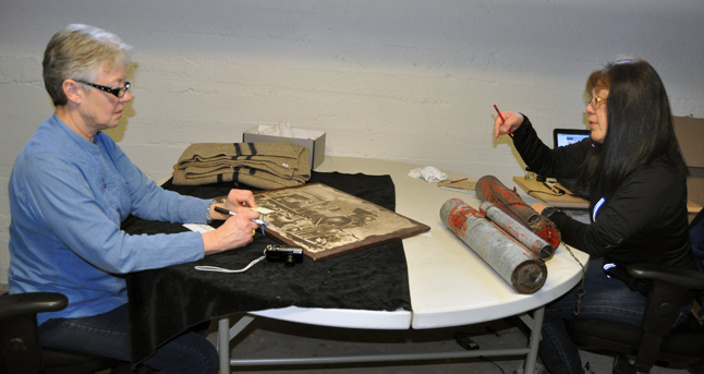 Volunteer Sheryl Wolgram talks with Harumi Harumi Sakiyama who has been contracted to re-examine and re-catalogue the Museum's 6,000 artifacts stored in the basement of the venerable building at First Street West and Boyle Avenue. David F. Rooney photo