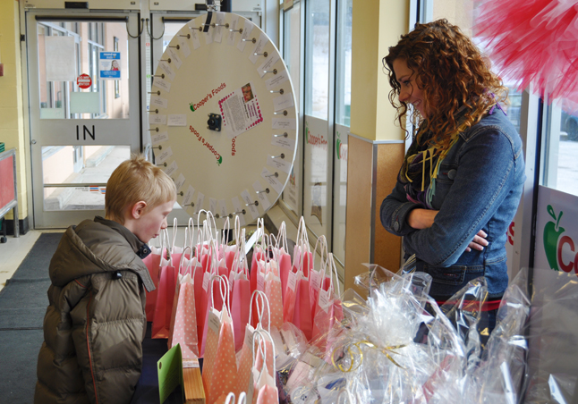 Young Corbin Martin checks out the prizes that where on offer at the special fundraiser at Cooper's for cancer victim Kendra Brown as Kendra's sister Rhonda Schmidt looks on. David F. Rooney photo