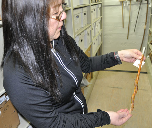 Harumi displays a fragment of a broken cane. A snake was carved onto the cane.  David F. Rooney photo
