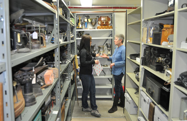 Harumi and Sheryl discuss where to store newly re-catalogued items. The storage shelving you see on the left and right are moveable components of the museum's new Hi-Cube storage system.  David F. Rooney photo