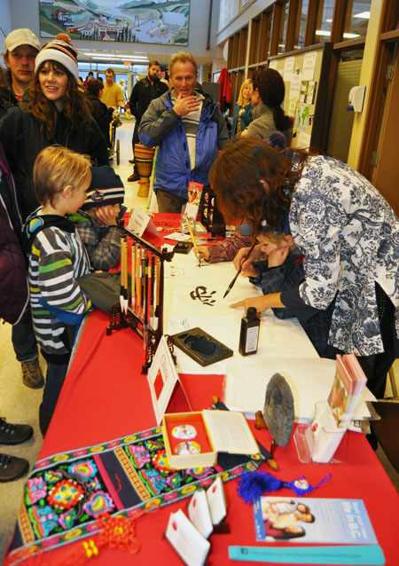 The English as a Second Language calligraphy table was a big hit with adults and children!  David F. Rooney photo