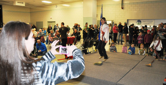 A spectator records two Metis dancers n her cell phone. David F. Rooney photo