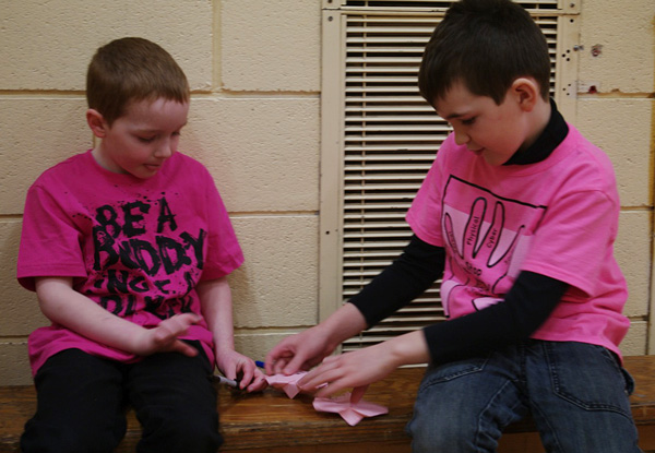 Josh Gale and Gavin Camara fold origami hearts during the buddy activity in the AHE gym . Photo by AHE Principal Todd Hicks