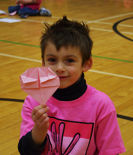 Jude Thompson smiles as he shows off his origami heart, a buddy activity for our Pink Shirt Day in the AHE gym on February 26. Photo by AHE Principal Todd Hicks