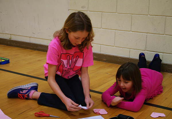 Emily MacLeod and Nicola Des Mazes work together on their origami heart buddy activity in the AHE gym. Photo by AHE Principal Todd Hicks