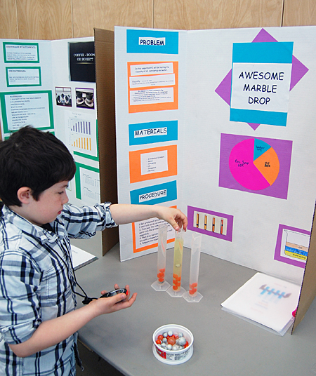 Caden Hedley demonstrates how different fluids affect the buoancy of marbles dropped into them. David F. Rooney photo