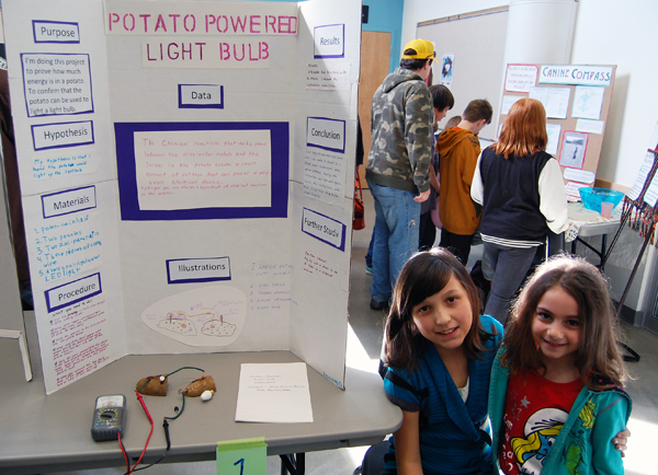 Anna Maria Aulisa's young cousin, Denise, (right) came to school to see her Potato-Powered Light Bulb experiment. David F. Rooney photo