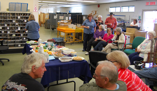 A Canada Post employee since 1979 Linda Jarche (center, left in the background) is retiring and friends and colleagues helped her celebrate on Tuesday, April 29, with wraps, cupcakes and a terrific chocolate cake from The Modern. David F. Rooney photo