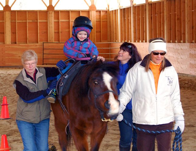 Zayden's happy smile speaks volumes as Tanya smiles up at him. Assistants Marcia Woods (left) and Donna Naprstek volunteer their time each week to help keep youngsters like Zayden safe while on horseback. David F. Rooney photo