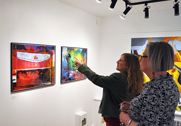 Carol Palladino (enter) and Margaret Pacaud admire Bruce Thomas' work Granny at the Opera, which is part of his exhibition, Next Passage Out, on display at the Revelstoke Art Gallery on Wilson Street until May 2. David F. Rooney photo