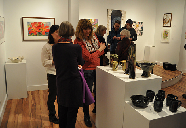 Ingrid Boaz admires the ceramics by Sandra Flood, Jacqueline Palmer and Nancy Geismar as Kendra Runnalls chats with Guinevere Battersby. David F. Rooney photo