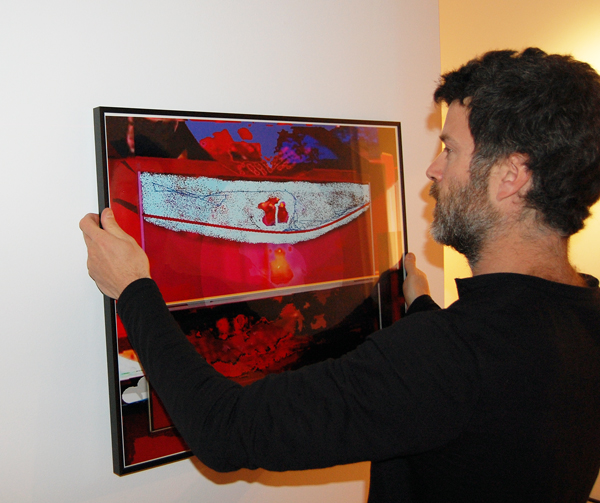 Bruce Thomas hangs one of the works from his solo show, Next Passage Out. David F. Rooney photo