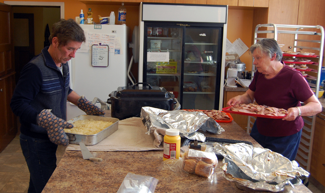 The United Church held a fund-raising dinner on Friday, April 25. Here, Bill McFarlane and Beth Campbell prepare to carry scalloped potatoes and baked ham out to the church hall where about 40 hungry people waited. David F. Rooney photo