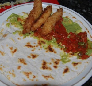Fish taco construction: guacamole, salsa on half the tortilla, fish strips on one quarter, before the folds.