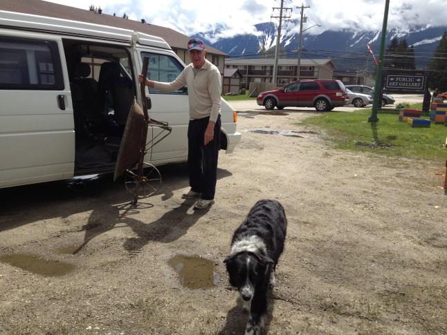 Volunteer Alan Dennis pulls out an antique wheelbarrow as his dog, Chester, investigates the planter construction.