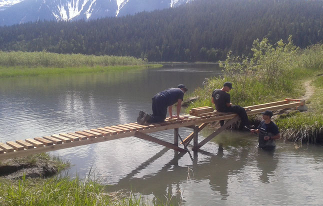 Monashee Unit crew members (from the left) Matt Smider, Cal Read and Jay Ellsworth along with Christian Foster, who is not in this picture because he's behind the camera, have done the community a great service by building this terrific footbridge down in the Greenbelt. Christian Foster photo