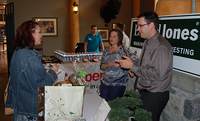 Chris Bostock (right) and his assistant Cathie Thacker talk with a potential customer for the Revelstoke branch of their investing and financial service business, Edward Jones. David F. Rooney photo