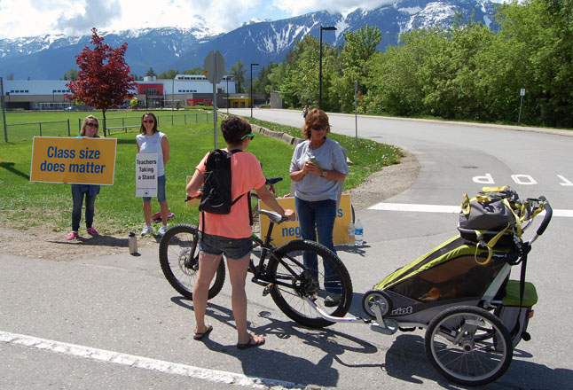 A mom with child in tow stops to wish striking teachers well at the entrance fo Begbie View Elementary School. David F. Rooney photo