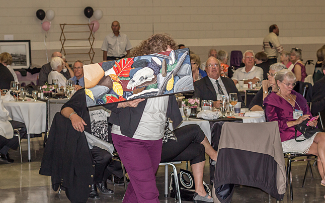 Rene Howe hides from the camera behind a beautiful donated painting. Jason Portras photo