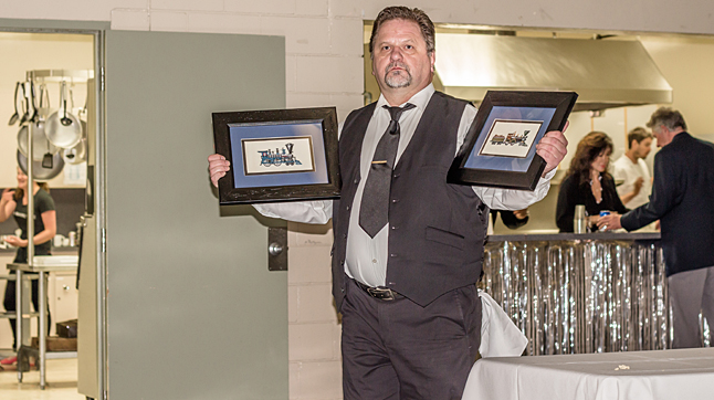 MC Bob Loeppky holds two cross-stitched train pictures in his best Vanna White pose. Jason Portras photo