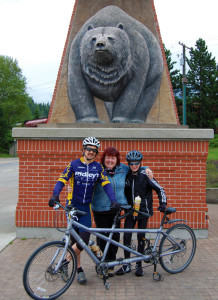 Melanie Melnyk is bursting with pride over her 12-year-old grand-nephew, Alex Weber, who is cycling from Vancouver to Calgary to raise money to help finance a well-drilling program in Mauretania. Here, she poses with young Alex  (right) and seasoned bicycle racer Jon Nutbrown (left) of Calgary, who has been cycling with the pre-teen while his dad drives a pilot vehicle with all of their gear. They rolled into Revelstoke on Monday night and then began pedalling their way eastward at about 7 am. David F. Rooney photo