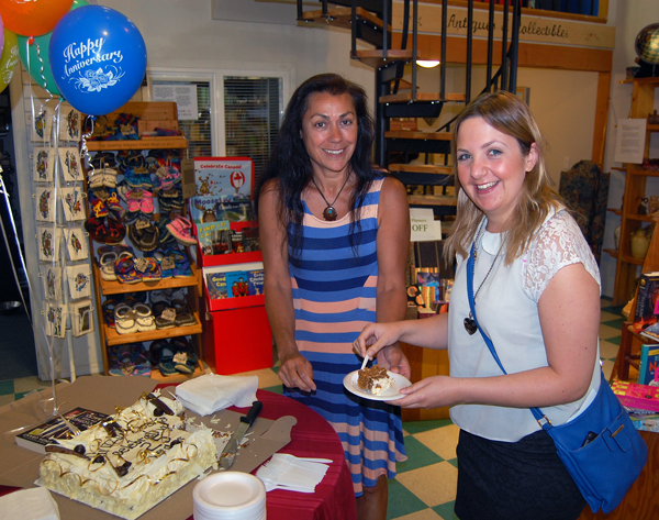 Vanessa Smith (left), owner of Grizzly Books & Serendipity Shop, serves up some delicious carrot cake to Emily Horkley on Thursday. The shop celebrated its 25th year in business with a the cake, balloons and lots of deals for customers. David F. Rooney photo