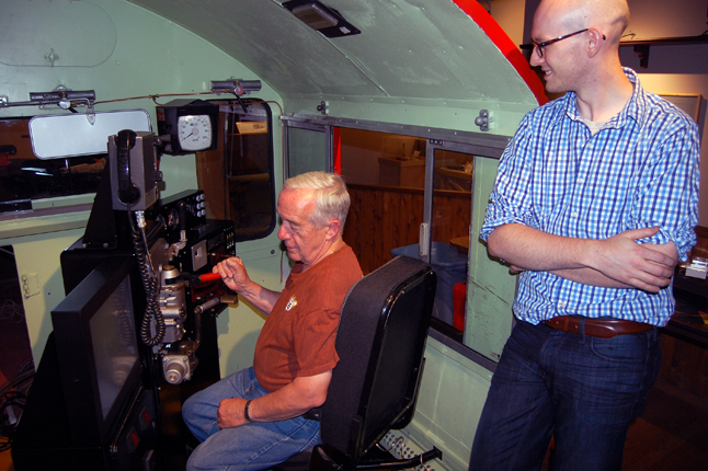 Railway Museum Volunteer Don Hawker sits in the driver's seat of the newly re-built and refurbished railway locomotive simulator at the Railway Museum as Jonathan Taylor of RST Instruments looks on. Taylor installed the new simulator that, according to volunteer George Hopkins is a faithful reproduction of the simulator he trained on when he joined the CPR many years ago. The new simulator features new sensors and effects that make it much more realistic than the old one, which was out of commission for the last two years. Give it a try for yourself at the museum! David F. Rooney photo