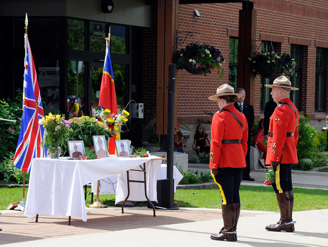 Const. Tanya Anthony and Cpl. Eric Page prepare to lay a rose before the photograph of Const. Douglas James Larche. Dusty Veideman