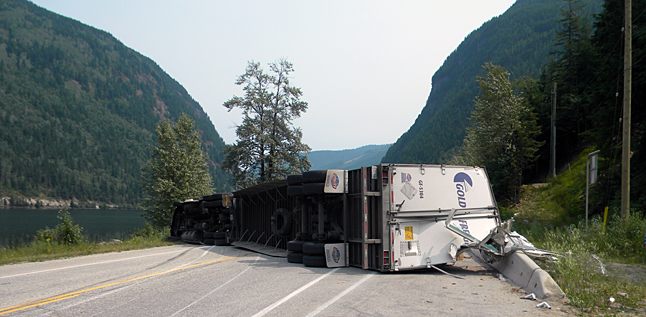 """The 22-year-old driver of an east-bound semi escaped with minor injuries after he lost control and rolled the vehicle, blocking all lanes of trafcuc at Three Valley Gap. """"The truck was hauling domestic cargo,"""" Staff Sgt. Kurt Grabinsky said in a statement released on Tuesday, July 15. """"The driver has been charged with Speed Relative to Conditions. Traffic was diverted into Revelstoke throughout this road closure from the east. West-bound traffic was held back on the western side of the accident. Drivers are advised to be aware of speed recommendation signs as speed was directly related to this incident. Photo courtesy of the Revelstoke RCMP"""