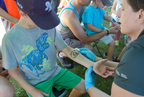 Ethan Schroeder gets a tattoo from Michelle Cole at the Parks Canada tent. David F. Rooney photo
