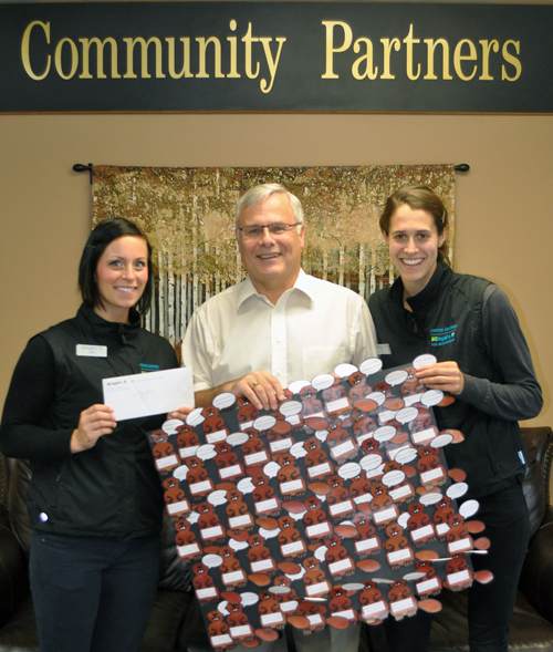BC Hydro's Alex Heeps (left) and Liz Craig pose with Community Connections Executive Director Craig T. Brown as they present him with a cheque for $1,520.40 and a wall hanging made by people who attended the recent Family Fun Days at the Revelstoke Dam. Every year the utility picks a charity to benefit from Family Fun Days when it donates its admissions to them. Community Connections staff also provided a barbeque and family activities during the July 12-13 event. The money raised during Family Fun Days will help underpin agency programs that do not receive core funding. David F. Rooney photo