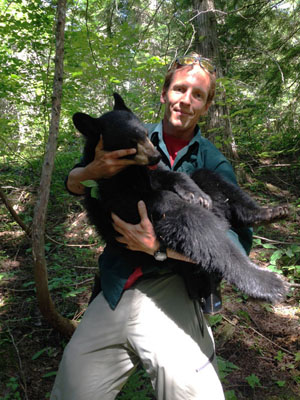 Parks Canada Resource Conservation Specialist Michel Beauchemin cradles the freshly orphaned bear cub in his arms. Alex Desjardins / BC Conservation Officer Service photo