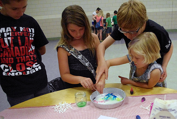 Awesome youth helpers Cameron McTaggart Erik Brosch help Halle Simpson and Eula Painter Bird make a milky rainbow, a science activity that explores the unique properties of a colloidal solution. Lucie Bergeron/Okanagan Regional Library photo