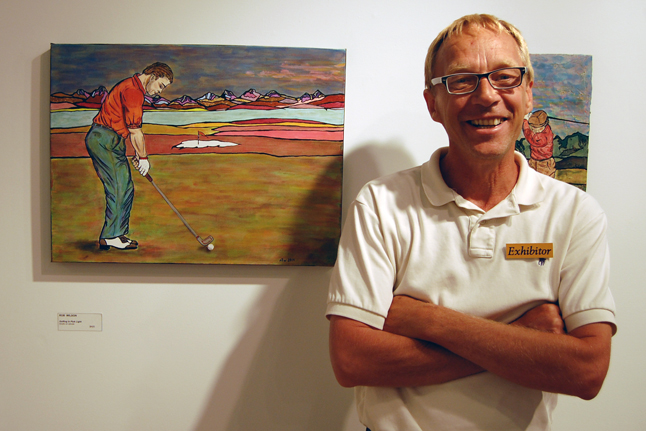 Rob Wilson poses with his painting, Golfing in Pink Light. Rob's exhibition of paintings about golf is whimsical and amusing. David F. Rooney photo