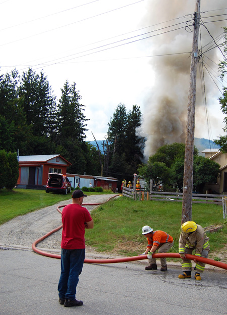A neighbourhood resident watches as a BC Hydro worker helps a firefighter adjust the position of a hose. David F. Rooney photo
