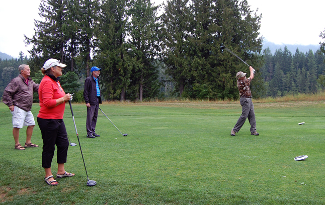 Robbie Moore tees off as his foursome partners look on. Moore and McKay's fathers were friends who served in the Second World War and later became a dentist and a doctor in post-war Revelstoke. David F. Rooney photo