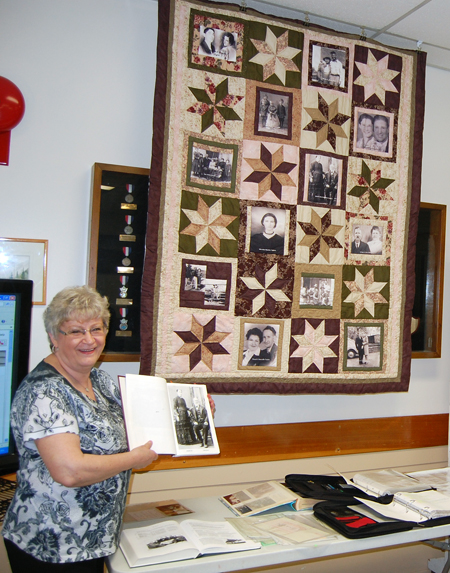 Ruth Boettger proudly shows off her home-made quilt that incorporated portraits of some of her ancestors. He can trace her line back to early 16th century England. David F. Rooney photo