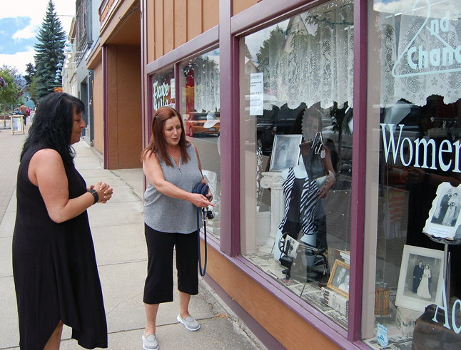 """Lisa Fik (center) tells Angela Waterson what she liked most about Angela's special Homecoming-themed window display at Escape Within. """"I've received a lot of comments about it,"""" Angela said. Lisa was most enthusiastic about the wedding photos of local newlyweds taken back in the 1920s and '30s. David F. Rooney photo"""