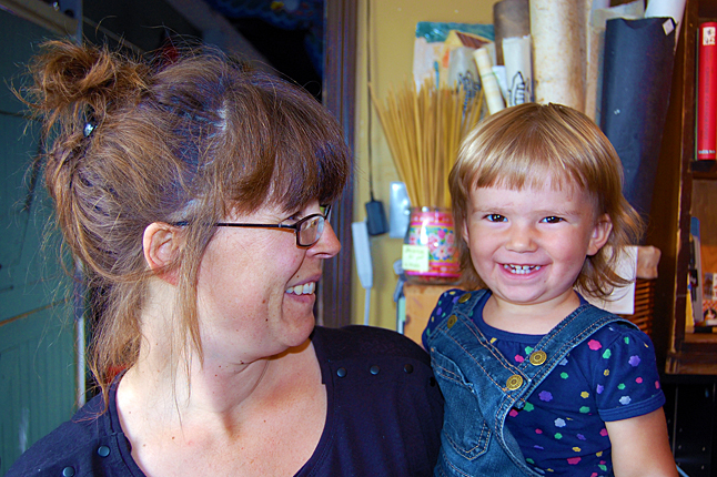 Happy toddler Maggie Johnston spent the first day of Homecoming with her mom, Gwen, welcoming people who wandered into Castle Joe Books and Art Supplies. David F. Rooney photo