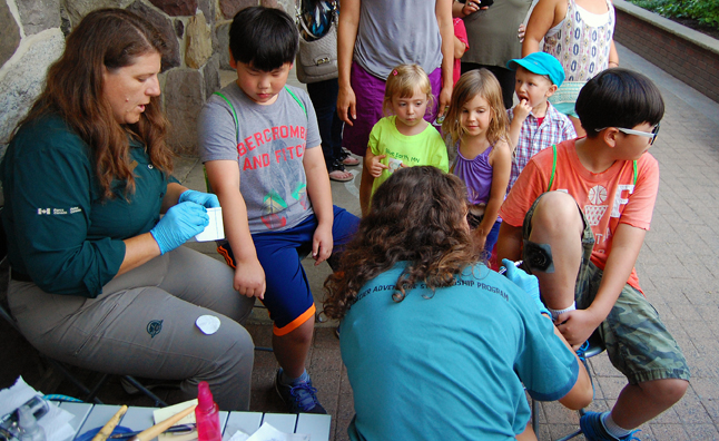 Parks Canada's Michelle Cole (left) and Hailey Christie-Hoyle created some nifty temporary tattoos for children at Grizzly Plaza as the next youngsters in line watched the process intently. David F. Rooney photo