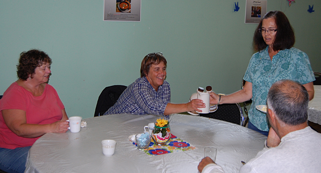 Patti Matsushita hands Bonnie Teed a syrup pitcher at the tail end of the logger's breakfast offered by the United Church Women on Saturday morning.  David F. Rooney photo