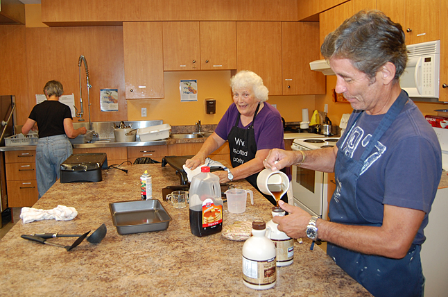 "Waste not, want not. Bill MacFarlane empties the syrup pitcher back into its original container during clean-up duty in the United Church's basement kitchen. Helen Shuttleworth (center) said 80 people enjoyed the logger's breakfast they offered on Saturday morning. ""We sold out,"" she said.  David F. Rooney photo"