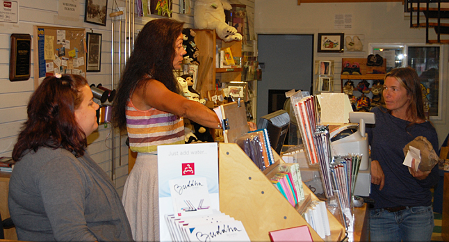 Grizzly Book & Serendipity Shop owner Vanessa Smith (center) chats with a customer. Vanessa said Homecoming has been good for business. There were about a dozen people wandering in an out of her shop when The Current dropped by shortly before lunch on Saturday. David F. Rooney photo