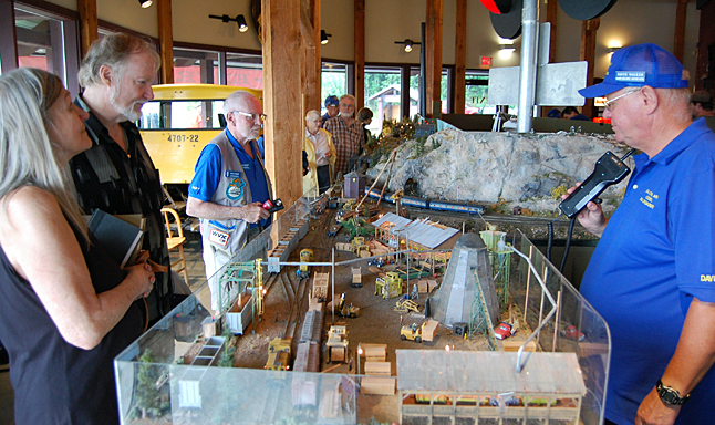 Saturday was also Family Day at the Railway Museum where Patrick O'Brien of Coldstream and Leona Friesen of Castlegar (left) admired the Salmon Arm Railroad Club's spectacular diorama, which was described for them by the club's David Walker (right).  David F. Rooney photo