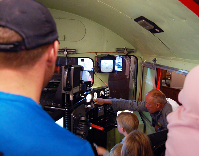 Railway Museum volunteer Ron Lind explains how the bells and whistles work in the really, really popular simulator. There was a lineup of at least eight people — most of them adults — who wanted to try the recently installed simulator.  David F. Rooney photo
