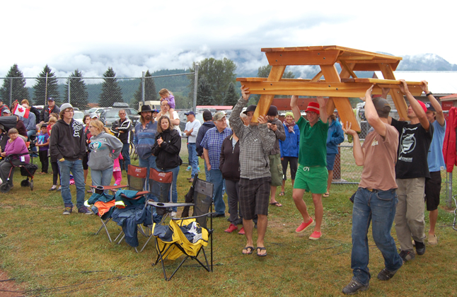 Volunteers hold aloft the hand-made picnic table which was on offer as a prize at Timber Days. David F. Rooney photo