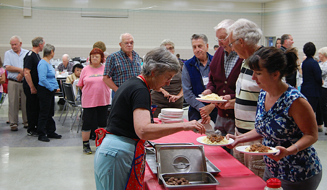 Pat Sieber (front left) serves up some fantastic-looking spaghetti sauce to a diner at the United Church's Community Spaghetti Dinner at the Community Centre late Saturday afternoon. David F. Rooney photo