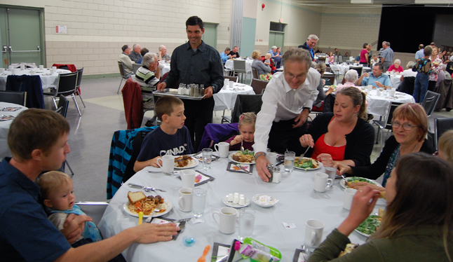 Rory Luxmoore (center, back) and Ken Jones went table-hopping to ensure that everyone had salt and pepper at the Community Spaghetti Dinner. David F. Rooney photo
