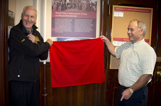 """Sam Olynyk and Mayor David Raven unveil the plaque that commemorates a shadowy episode from the First World War: Canada's decision to imprison thousands of immigrants from the Austro-Hungarian, German and Ottoman empires as """"enemy aliens."""" Revelstoke was — briefly — the site of one of the internment camps. Sarah Mickel photo"""