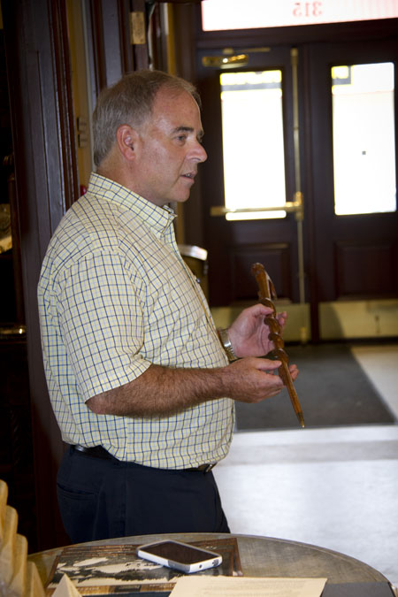 Mayor David Raven displays a cane hand-carved for a guard by one of the prisoners in the Revelstoke Camp that is kept in the mayor's office at City Hall. Sarah Mickel photo